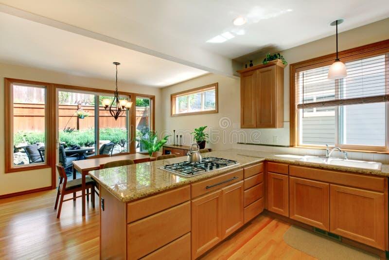 Brown e sala branca da cozinha com assoalho de folhosa, armários e área comer imagem de stock royalty free