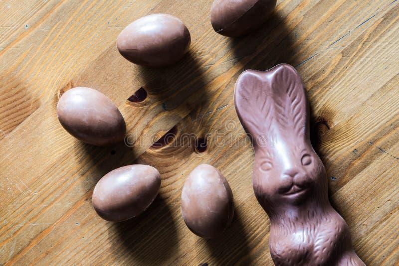 Brown Easter czekoladowy królik i jajka na drewnianym stole zdjęcia royalty free