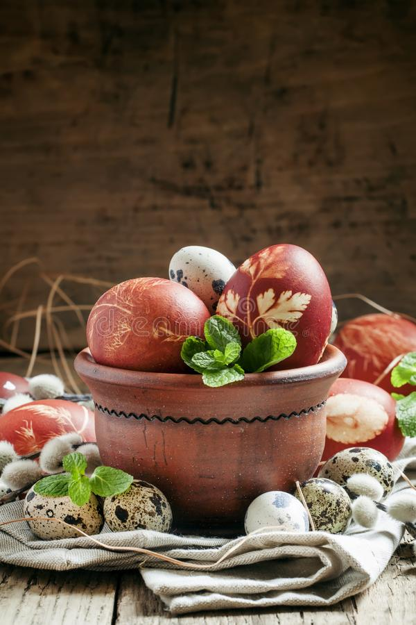 Brown easter egg with a pattern with small speckled quail eggs i. N a clay bowl with mint leaves and sprigs of willow fluffy, still life in a country style stock photo