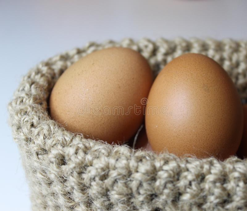 Easter eggs in the basket of hemp on white background stock photo