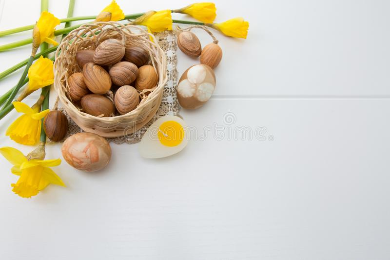 Brown easter eggs in basket and yellow daffodils. stock images