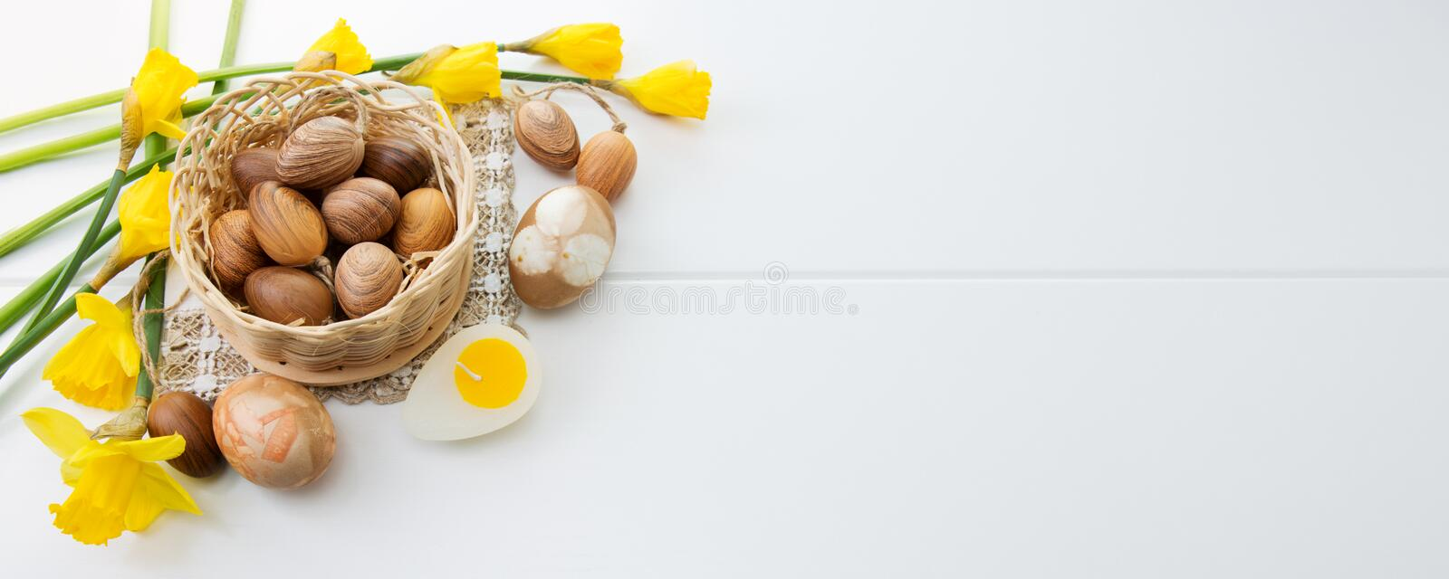 Brown easter eggs in basket and yellow daffodils. royalty free stock photos