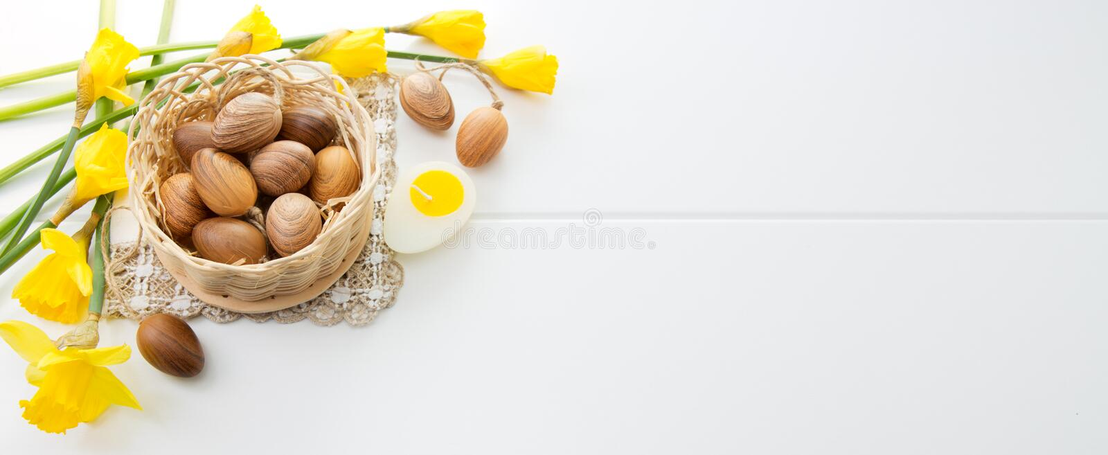 Brown easter eggs in basket and yellow daffodils. royalty free stock image