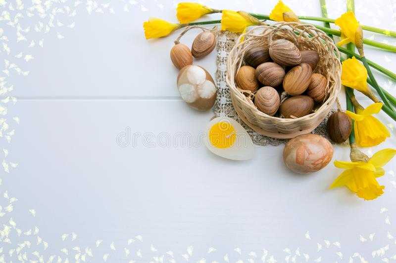 Brown easter eggs and yellow daffodils. Easter background. stock image