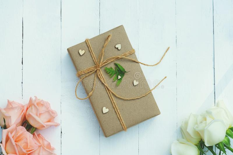 Brown eco friendly gift box decorated with soft pink and white rose on white wooden table, sweet lovely present valentine concept stock photography