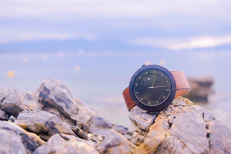 Brown ed orologio analogico rotondo nero sulle rocce beige fotografia stock libera da diritti