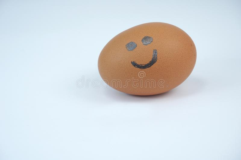 Brown egg with smile drawn on it with a sharp pencil stock image