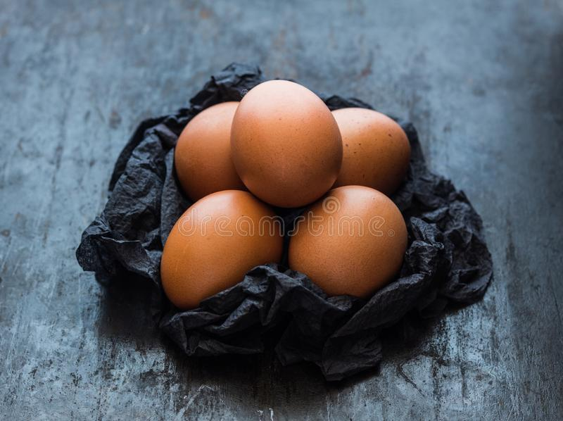 Brown eggs on a black napkin on dark background royalty free stock images