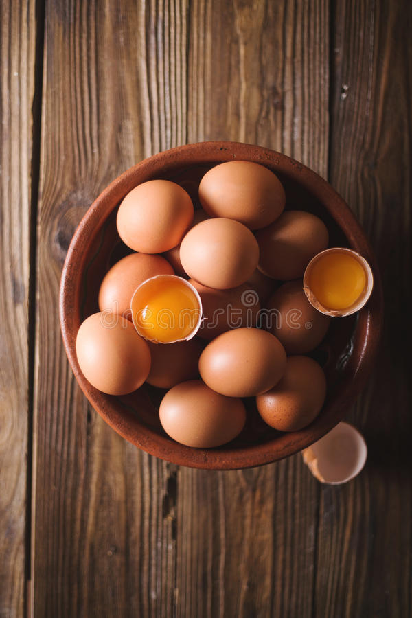 Brown eggs and broken eggs in a brown ceramic bowl on wooden table. Rustic Style. Eggs. royalty free stock images
