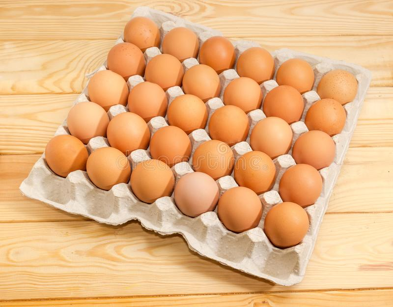 Brown eggs in the cardboard egg tray on wooden surface royalty free stock photography
