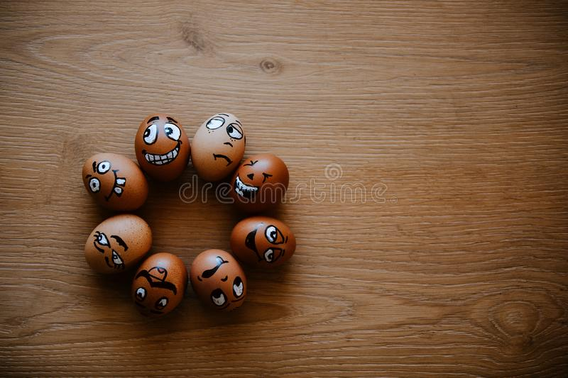 Brown eggs with different faces expressions painted on egg shell. Crazy eggs lying in a circle on wooden background stock image