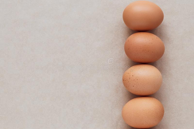 The brown eggs on a neutral paper background. A group of chicken eggs on beige table. Card, frame with text space. royalty free stock photography