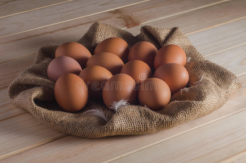 Brown eggs on a sacking on a wooden table.  stock photo