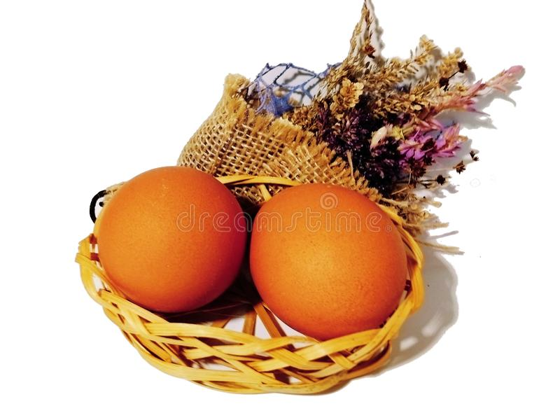 Brown eggs on a white background. Isolated. Brown eggs in a small wattled basket with dried flowers on a white isolated background royalty free stock photo