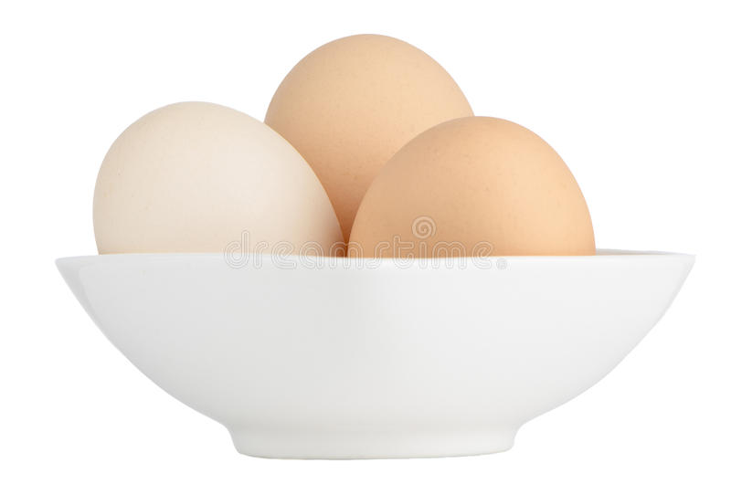 Brown eggs in white ceramic bowl stock photography