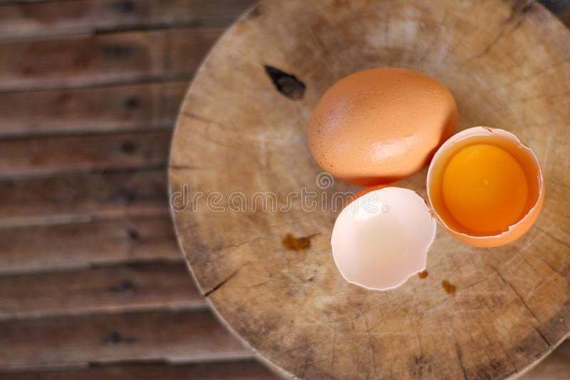 Brown eggs on a wooden chopping board There is a yolk in the egg shell. The brown egg has a drop of water because it is removing stock photos