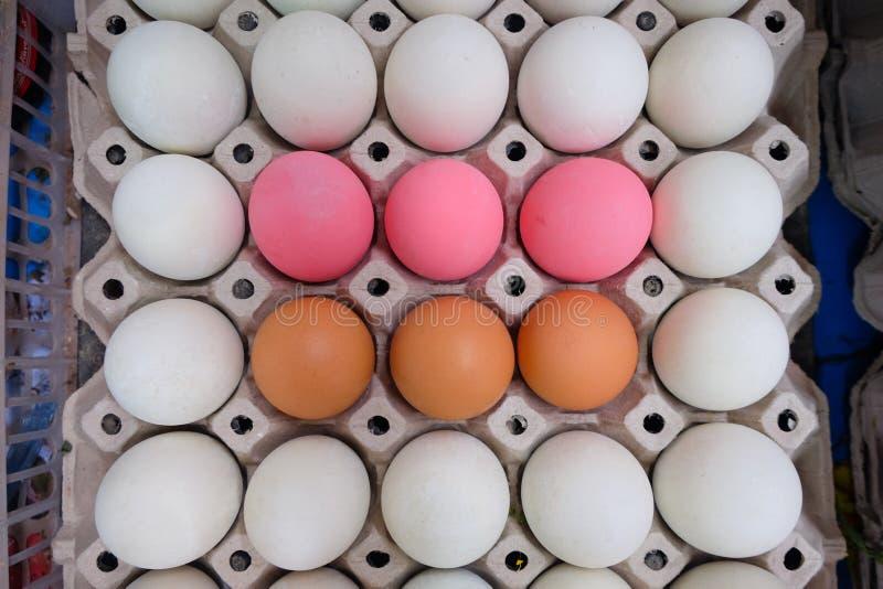 Brown-Eiweiße eier und rosa Eier im schwarzen Behälter stockfotografie
