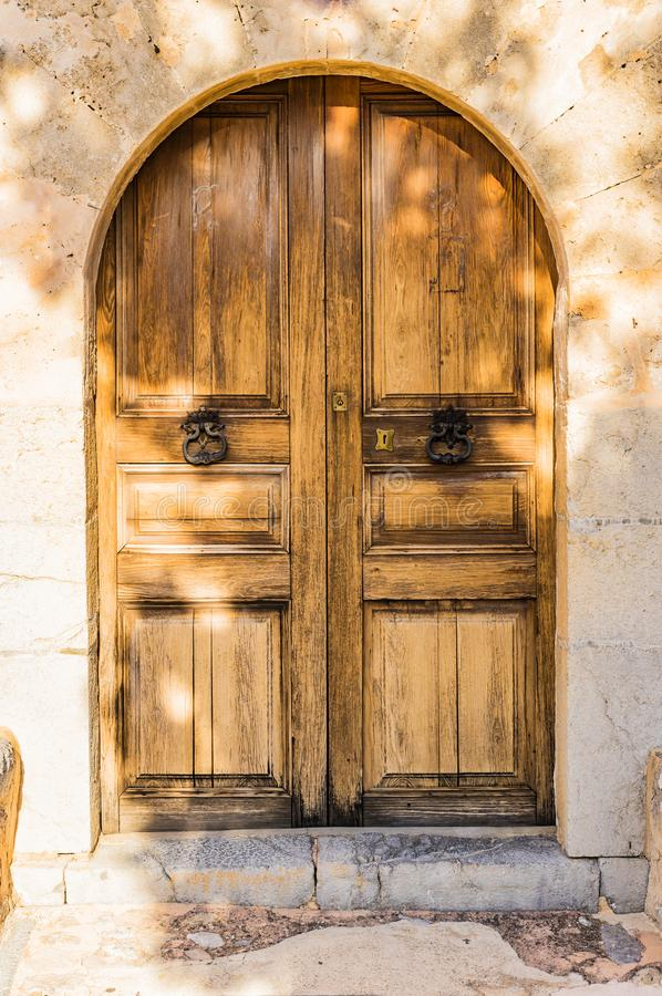 Elegant wooden entry door with stone arch of an old Villa stock images