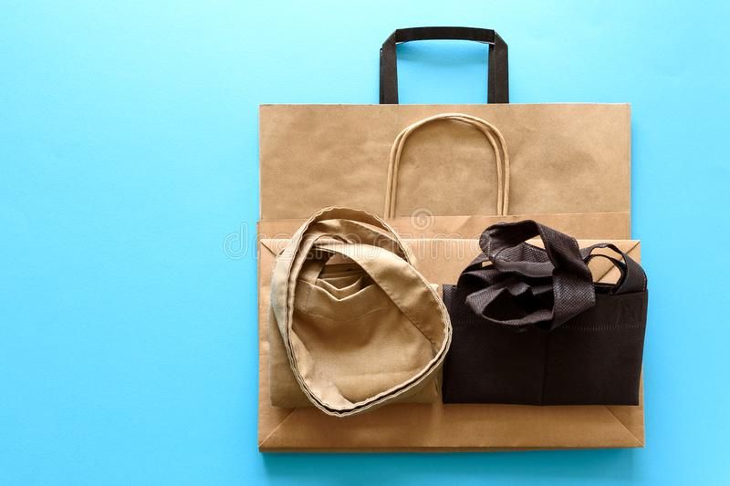 Brown empty kraft paper and linen case bags on blue background. Top view. Eco packaging or packaging of meals concept.  royalty free stock photos