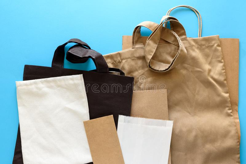 Brown empty kraft paper and linen case bags on blue background. Top view. Eco packaging or packaging of meals concept.  stock photo