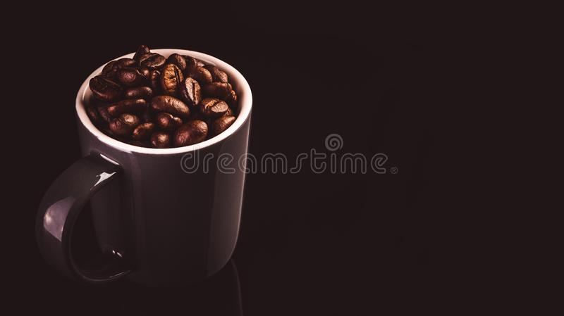 Brown espresso cup with coffee beans isolated on black background royalty free stock images