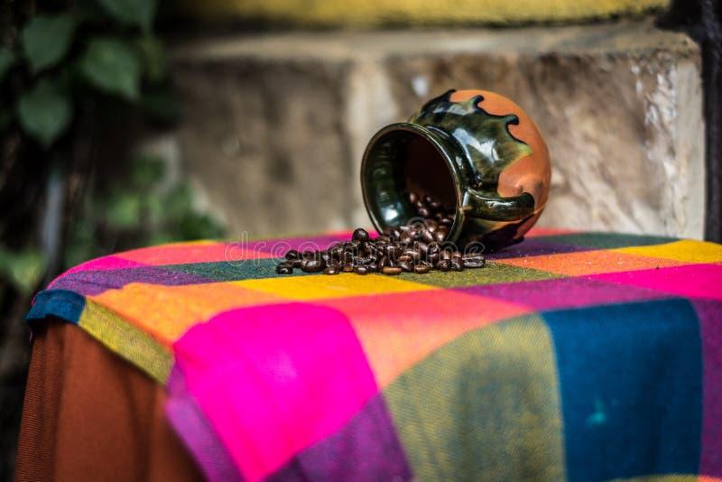 Brown et café en céramique Bean Rack de noir sur le textile vert et jaune rose image libre de droits