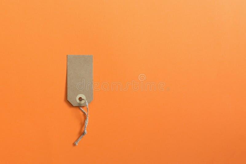 Brown etiquette of kraft cardboard on an orange background. Mock royalty free stock photo