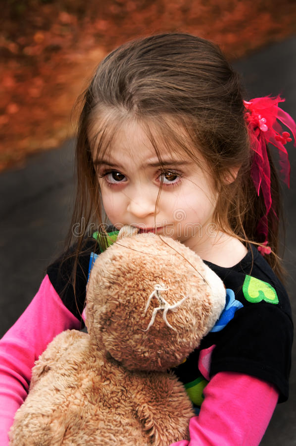 Brown eyed girl with her teddy bear royalty free stock photo