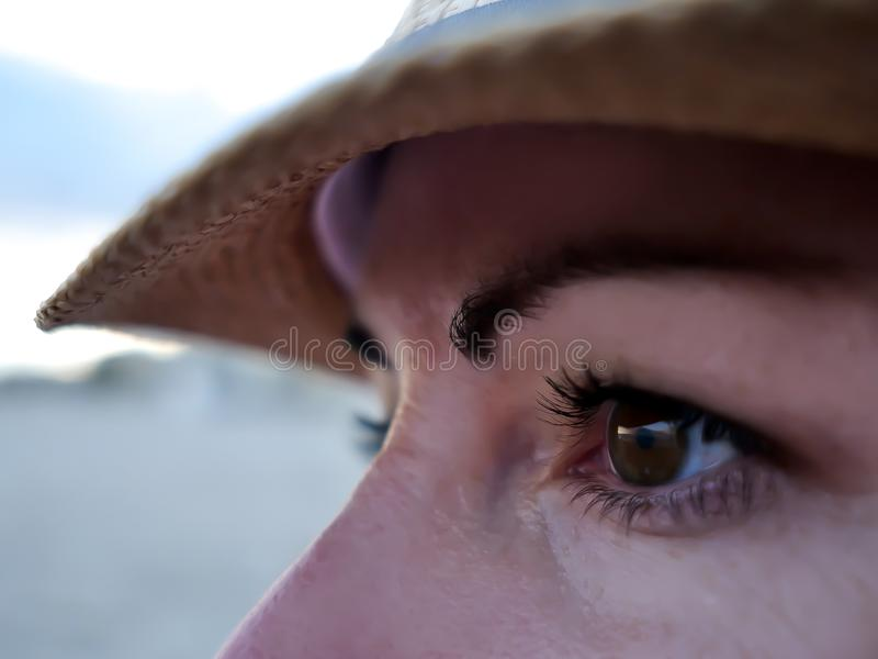 Brown eyes of a young woman in a hat looking to the side, close-up royalty free stock photo