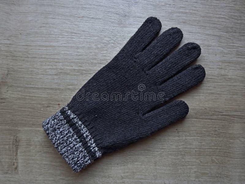 Brown-Farblegten handgestrickte warme Wollwinter-Handschuhe flach auf die hölzerne Hintergrund-Oberfläche lizenzfreie stockfotografie
