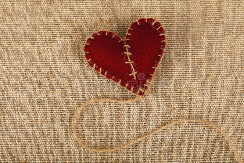 Brown felt craft heart over canvas close up. Valentine Day template, one handmade brown felt craft stitched toy heart with jute twine thread on linen canvas stock photos