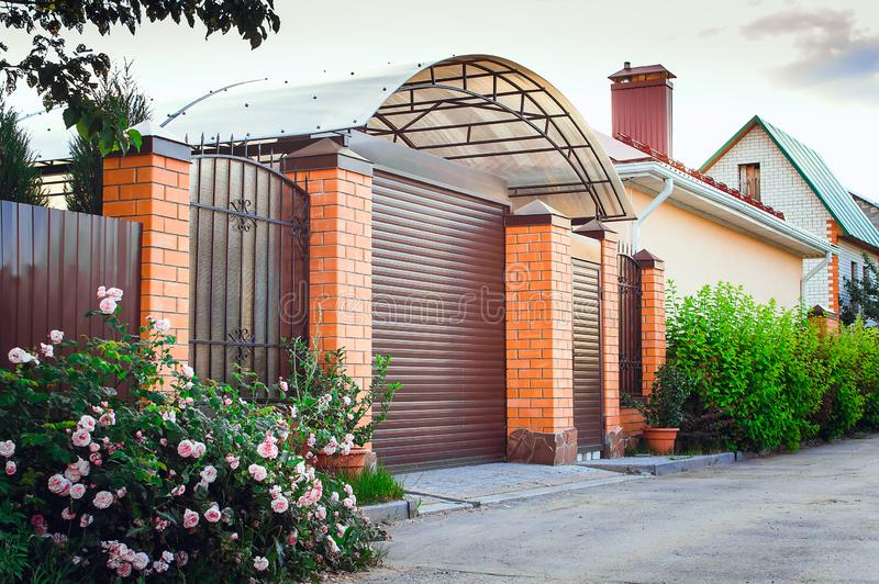 A brown fence made of polyprofile with a canopy in a modern style with brick columns, the design of a country house royalty free stock photo