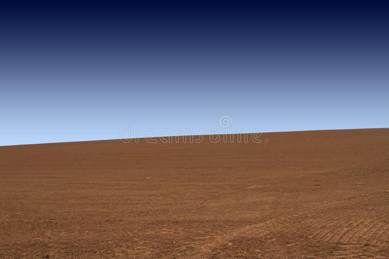 Brown field and blue sky - graphic photograph. Ploughed field and smoothed. A gradient blue sky royalty free stock photo