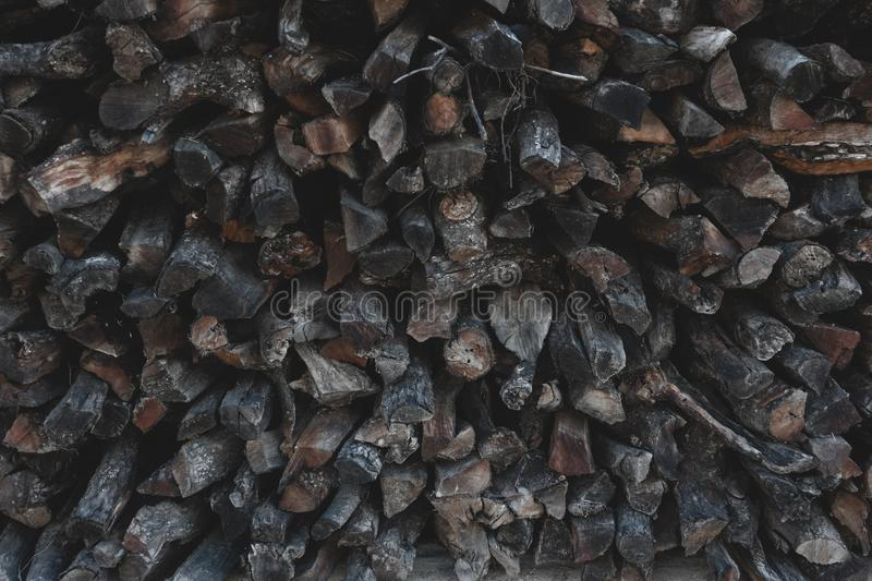 Brown firewood dry chopped wood logs or piles stacked for winter. On wooden background stock photo