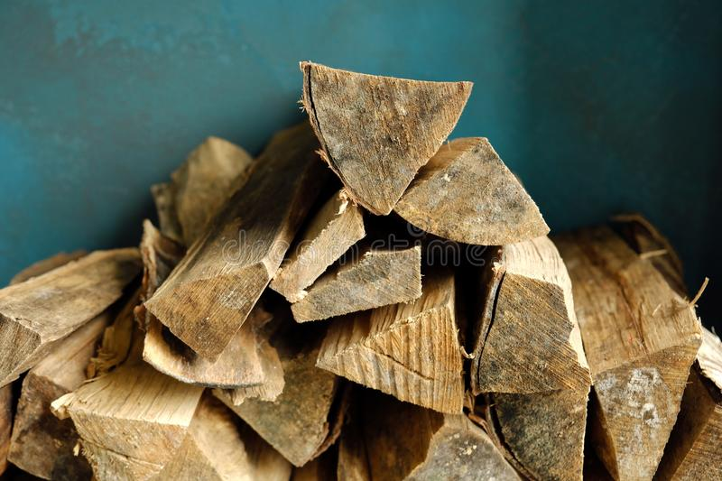 Brown firewood for the fireplace on a blue background. View stock photography