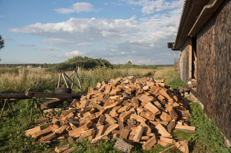 Brown firewood on green background in the summer farm with work house. With blue sky and green grass stock photography