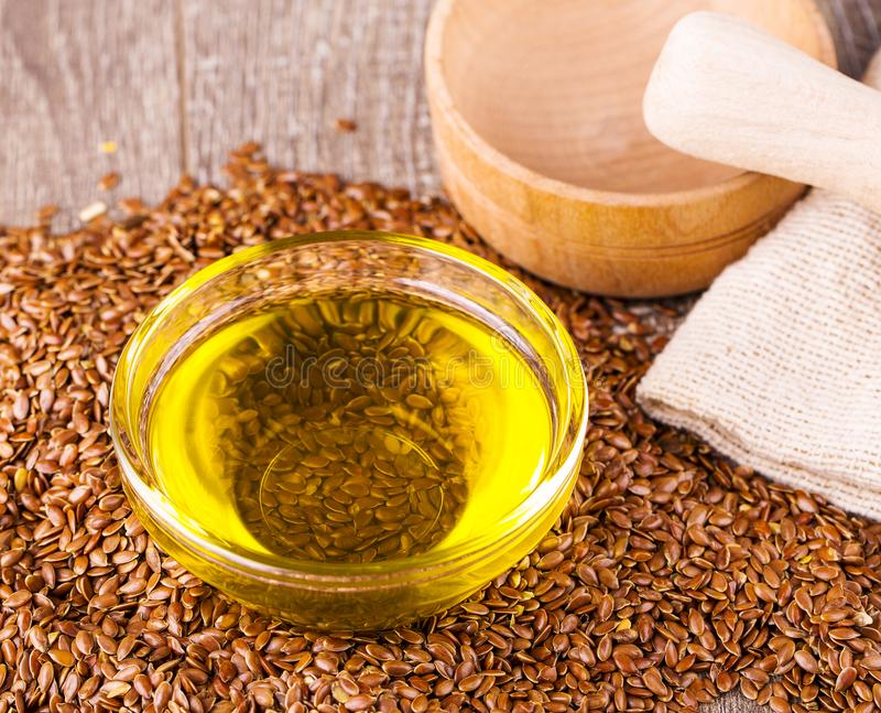 Brown flax seeds and flaxseed oil on wooden table. Brown flax seeds and flaxseed oil on table stock photos