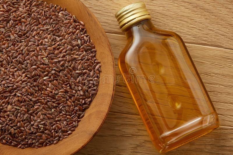 Flax seeds in bowl and flaxseed oil in glass bottle on wooden background, top view, close-up, selective focus. Brown flax seeds in wooden plate and flaxseed oil stock image