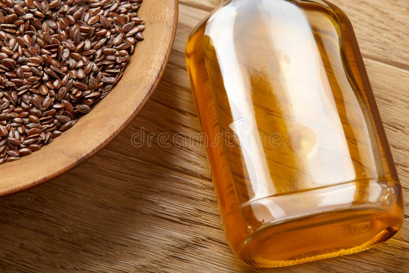 Flax seeds in bowl and flaxseed oil in glass bottle on wooden background, top view, close-up, selective focus. Brown flax seeds in wooden plate and flaxseed oil royalty free stock photography