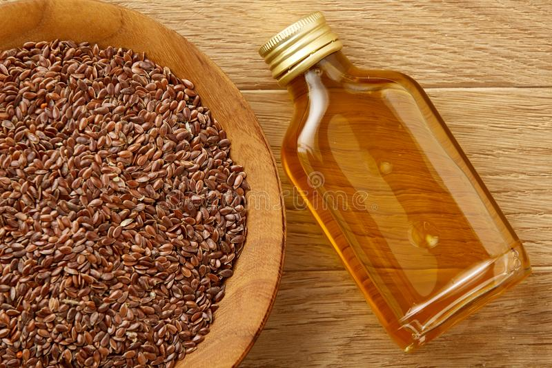 Flax seeds in bowl and flaxseed oil in glass bottle on wooden background, top view, close-up, selective focus. Brown flax seeds in wooden plate and flaxseed oil royalty free stock images