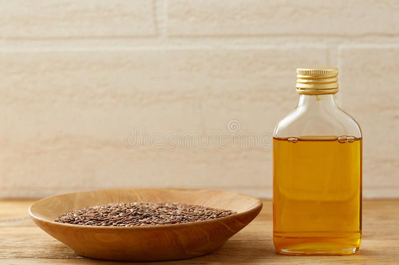 Flax seeds in bowl and flaxseed oil in glass bottle on wooden background, top view, close-up, selective focus. Brown flax seeds in wooden plate and flaxseed oil stock photos