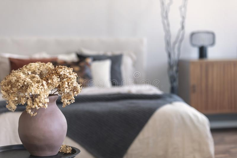 Brown flowers in pottery vase on metal nightstand next to king size bed in scandinavian bedroom interior royalty free stock photo