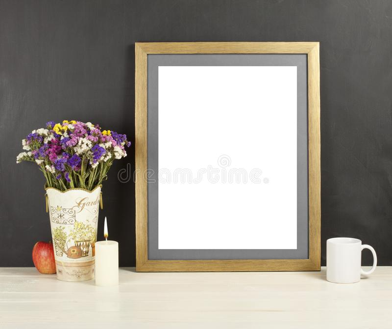 Brown frame mockup with field flowers in vase, apple, mug and ca. Ndle. Empty frame mock up for presentation design. Template framing for modern art royalty free stock photos