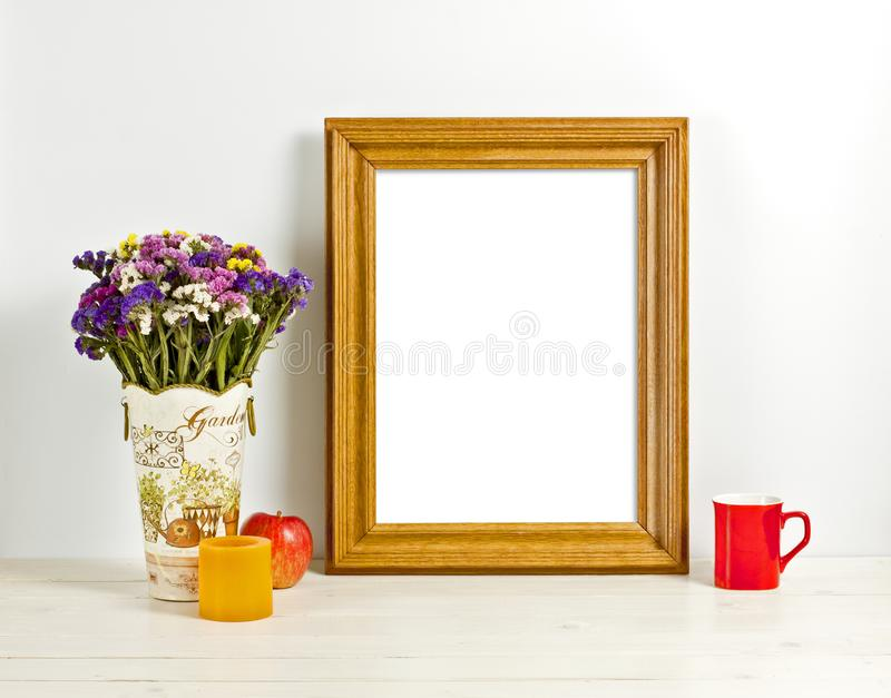 Brown frame mockup with field flowers in vase, apple, mug and ca. Ndle. Empty frame mock up for presentation design. Template framing for modern art royalty free stock photography