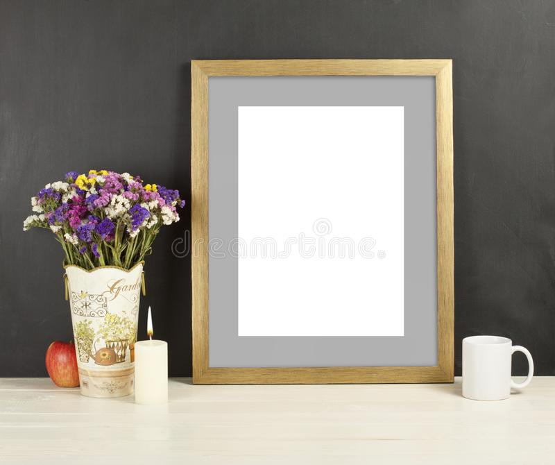 Brown frame mockup with field flowers in vase, apple, mug and ca. Ndle. Empty frame mock up for presentation design. Template framing for modern art royalty free stock image