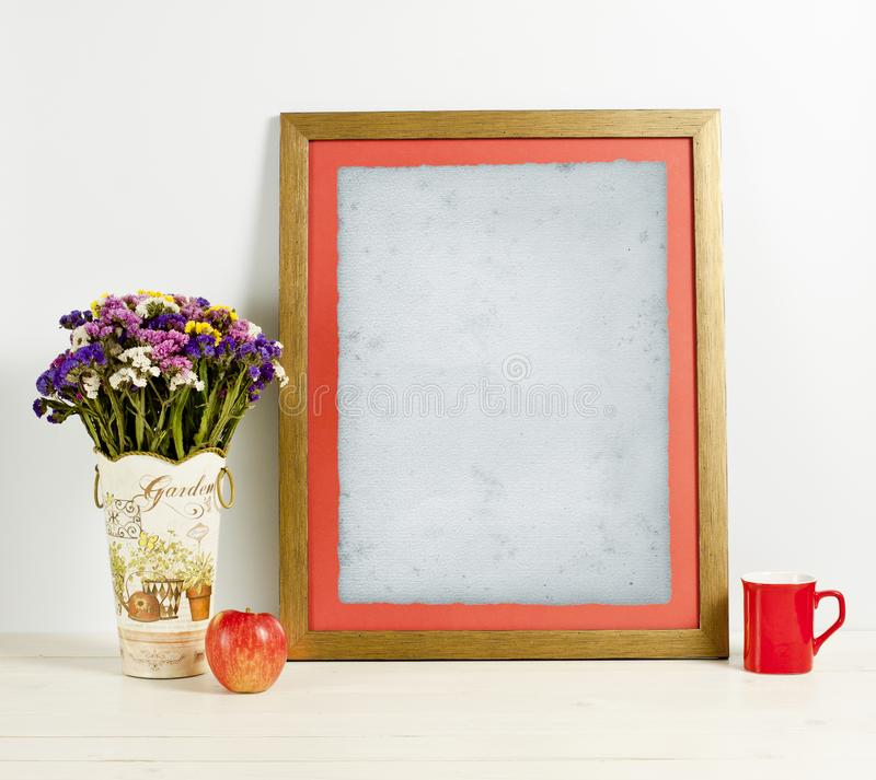 Brown frame mockup with field flowers in vase, apple, mug and ca. Ndle. Empty frame mock up for presentation design. Template framing for modern art stock images