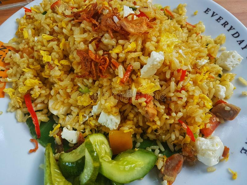 Brown fried rice with with chili,cucumber and fried onion in the white plate on the wooden table. Top view close up details. stock photos