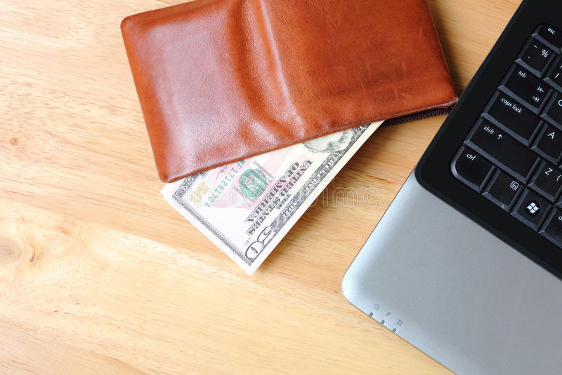 Brown-Geldbörse mit Dollarbargeld und Notizbuch auf sauberem hölzernem backgro stockfotografie