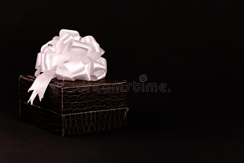 Brown gift box decorated with white ribbon isolated on a dark background royalty free stock photos