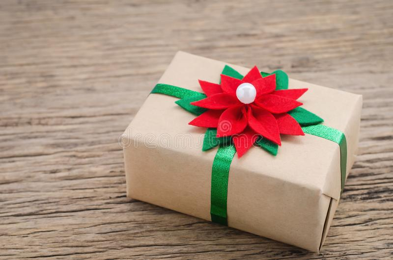 Brown gift box with red and green Christmas flower ribbon royalty free stock images